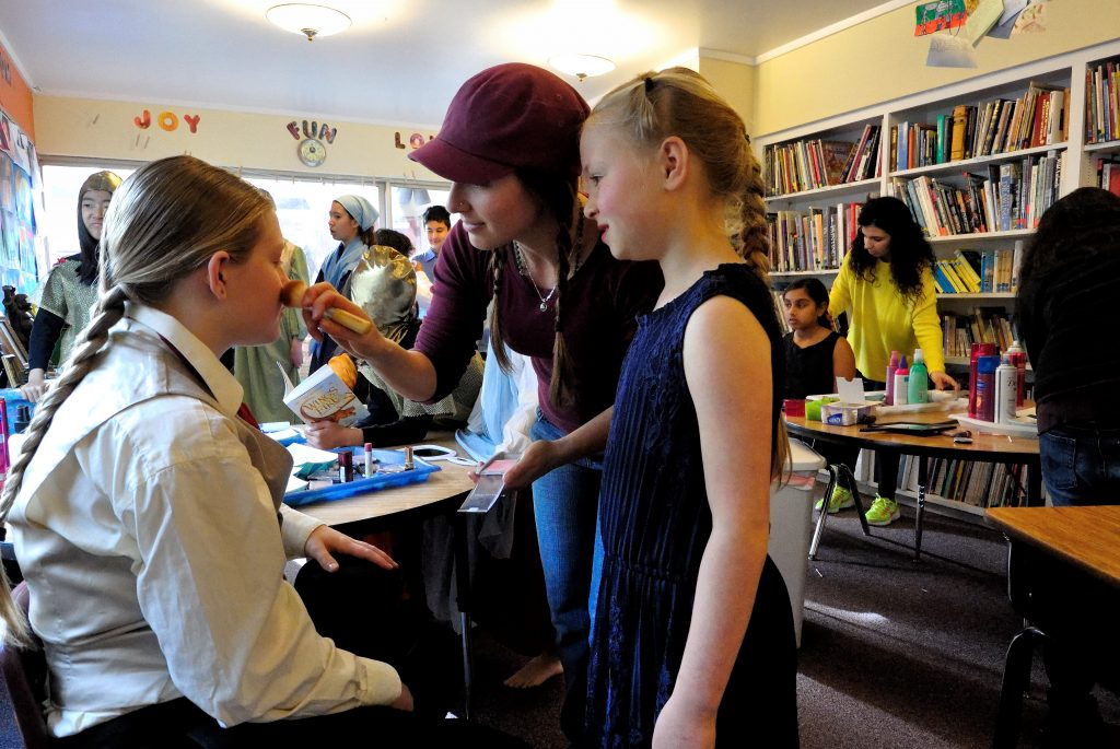 Students at Living Wisdom School get makeup applied before a performance of the all-school play, <em>Living Waters: The Story of Bernadette of Lourdes</em>.